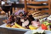Feast like the Gods w/ a Traditional Kontosouvli Spit Roast Feast + Wine at Yia Mas Greek Taverna! Think Meat, Haloumi, Dolmades, Dip, Pita & More